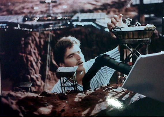 An artist makes adjustments to the Martian landscape miniature set.